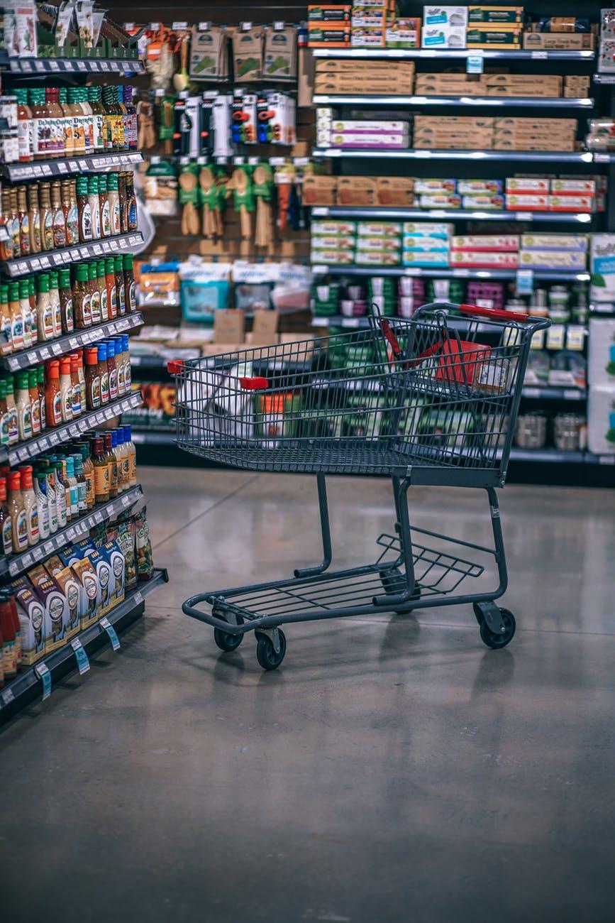 empty gray metal shopping card near assorted plastic bottles